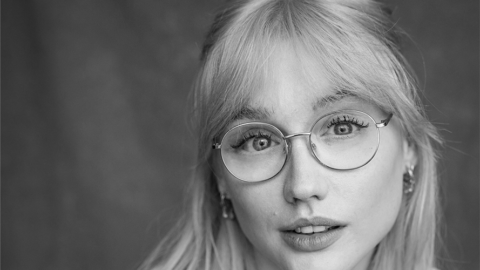 A portrait black and white photograph. Alice wears clear circlular glasses, she has a fringe and her hair is half up half down.